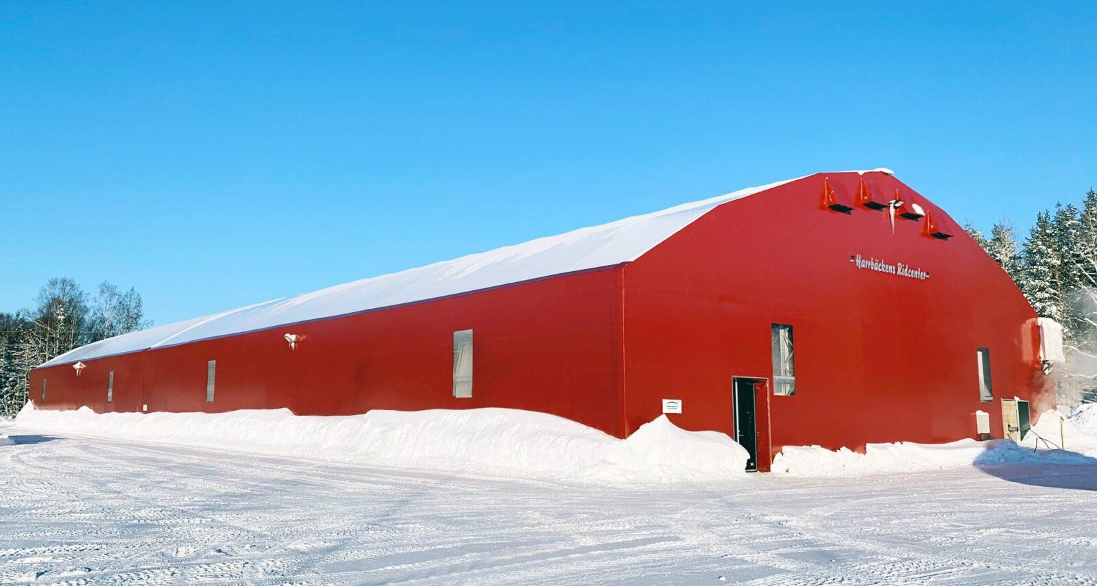 Snötäckt ridhall med röda fasader