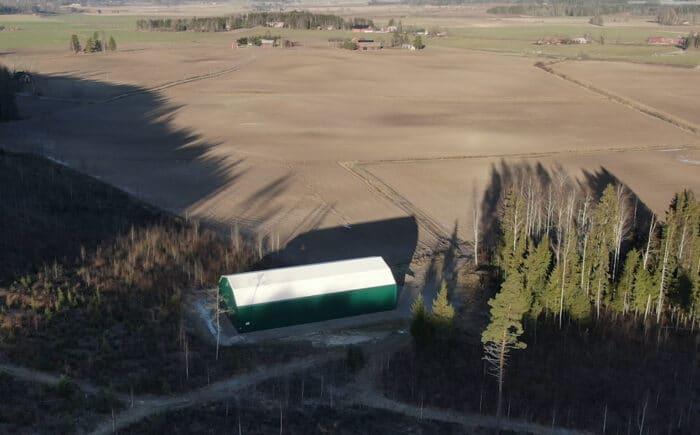 En grön maskinhall till lager av jordbruksmaskiner