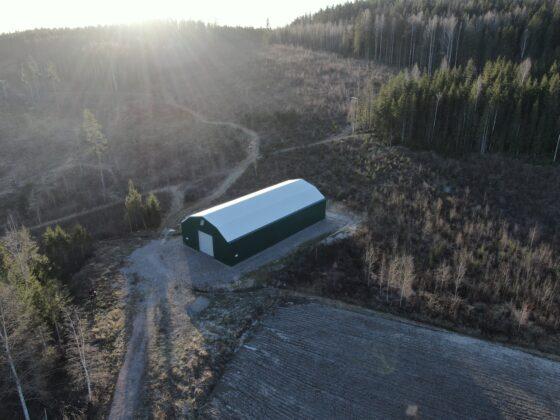 Grön maskinhall utanför Hedemora till förvaring av jordbruksmaskiner