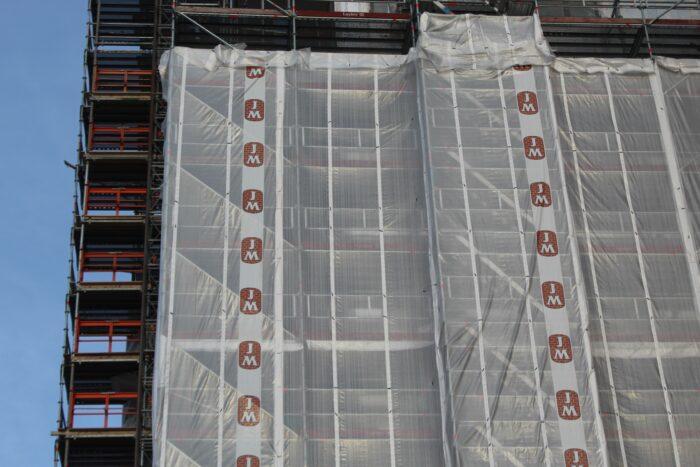 Byggställning klädd med profilerad sommarväv (ställningsduk / ställningsplast) på JM:s byggarbetsplats i Kallhäll