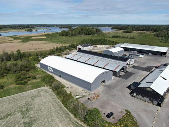 Gråa hallar hos EHL Prolist. Blå himmel och sjö i bakgrunden. Bild tagen med drönare på anläggningen i Möklinta