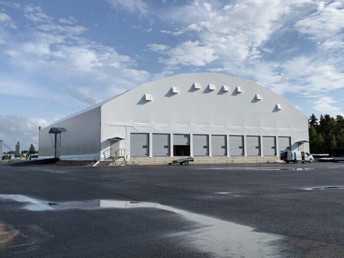 En grå hall med nio synliga lastportar (9 till på baksidan) på Sandahlsbolagens anläggning i Värnamo. Hallen fungerar som omlastningscentral.