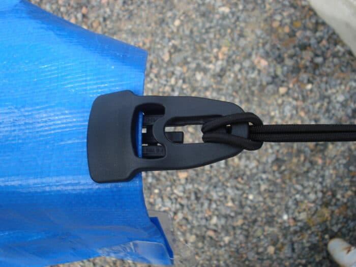 Presenningsklämman Holdon® Midi Clips - Även kallad öljettklämma - som spänner åt en press.